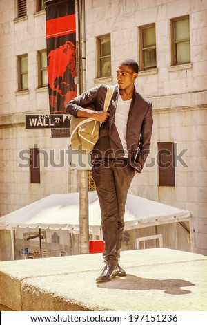 Street Fashion. Wearing a white under wear, fashionable jacket, pants, leather shoes, carrying a shoulder bag,  a young black college student is standing on Wall Street, confidently looking forward.  - stock photo