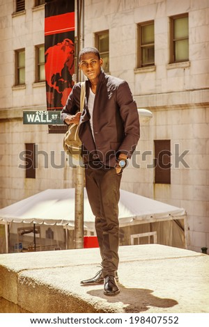 Street Fashion. Wearing a white under wear, fashionable jacket, pants, leather shoes, carrying a shoulder bag,  a young black college student is standing on Wall Street, hopefully looking at you. - stock photo