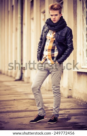 Street fashion. Young fashionable man in full length guy with stylish haircut casual clothes posing outdoor on cityspace background. Aged tone - stock photo