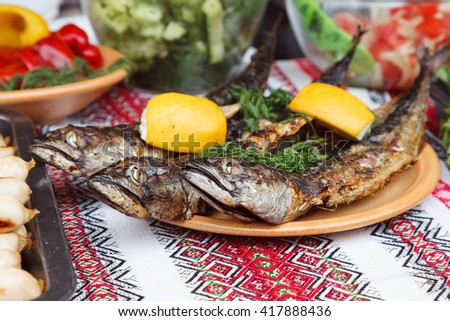 Street food. Fried fish on a tray. Against the background of a bowl with vegetables and salads