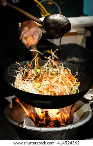 street food. fried noodles in a wok with chicken and shrimp on the open fire - stock photo