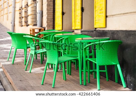 Street green cafe tables and chairs in European city - stock photo