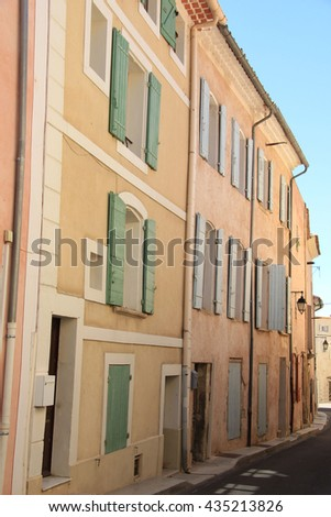 Street in a Provencal city, colored houses in a row - stock photo