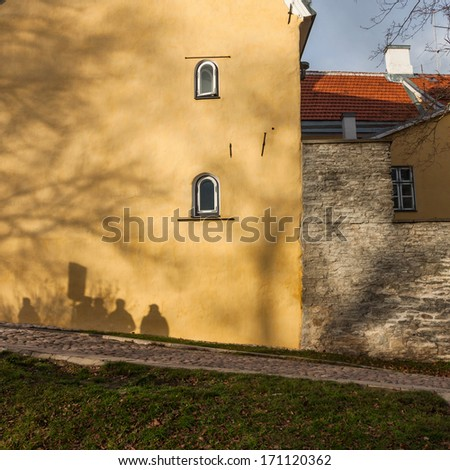 Street in old town of Tallinn, Estonia. Tourists shadows on the wall