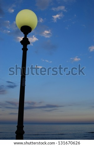 Street lamp at dusk on blue cloudy sky in front of the sea - stock photo