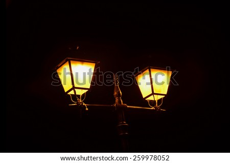 Street lamp iluminated in yellow. Urban illumination for night - stock photo