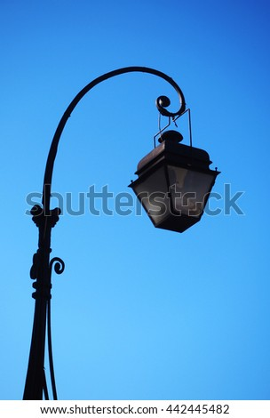 Street lamp post on clear blue sky background. - stock photo