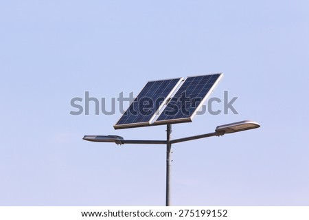 street lamp post with solar panel energy (against blue sky background) - stock photo