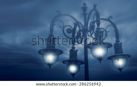 street lamp shining at night against cloudy sky - stock photo