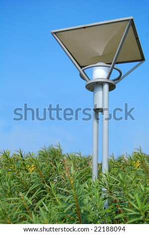 street lamp stand in green plants with blue sky background
