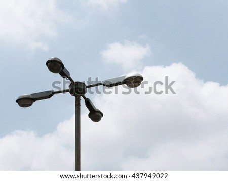 Street Lamppost with four arms on cloudy blue sky - stock photo