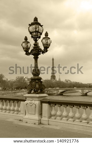 Street lantern on the Alexandre III Bridge with Eiffel Tower in Paris, France, sepia picture. - stock photo