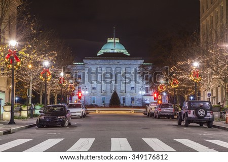 street level scene at night of Raleigh, North Carolina and capital building - stock photo