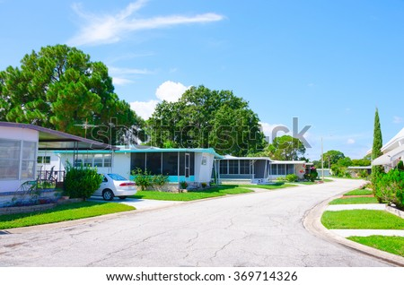 Street level view of a very well kept mobile home trailer park neighborhood in central Florida with nice yards and big green trees on a beautiful sunny afternoon - stock photo
