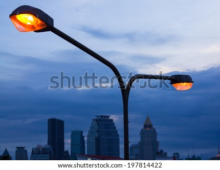 Street light against Bangkok in twilight background - stock photo