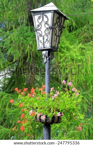 Street light decorated with colorful flowers on a street in South Tirol, Austria - stock photo