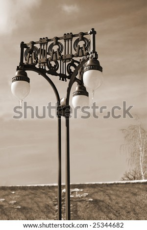 Street light in winter time with blue cloudy sky as background - Sepia tone - stock photo