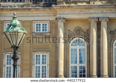 Street light with crown on top. Beautiful historical retro metal lantern on Amalienborg Palace background. Vintage angular lamppost with edges in Copenhagen,Denmark. Wrought iron lamp. Focus on lamp.