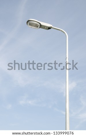 Street light with halogen lamp against blue sky - stock photo