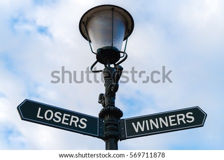 Street lighting pole with two opposite directional arrows over blue cloudy background. Losers versus Winners concept.
