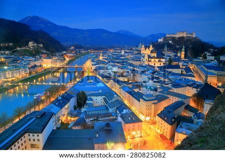 Street lights illuminate the old town, church buildings and medieval castle, Salzburg, Austria - stock photo