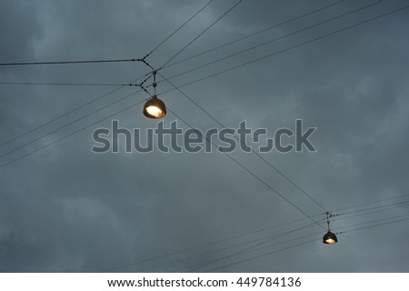 street lihjt on wire, on dark sky and its almost night.  - stock photo