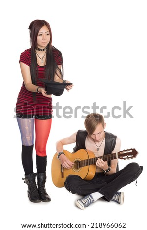 Street musicians play and sing on guitar. Asian woman and Caucasian man.  - stock photo