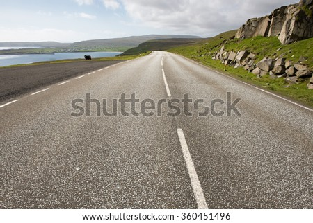 Street on the Faroe Islands, with landscape, ocean, rocks on Sandoy close to Sandur