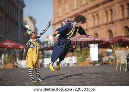 Street performance of clowns, learning to fly - stock photo