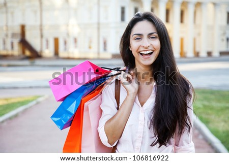 Street photo of beautiful woman with shopping bags - stock photo
