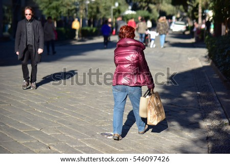 Street photographer: Savona, Italy, December 2016: people coming out of shops with gift bags and parcels during the Christmas holidays