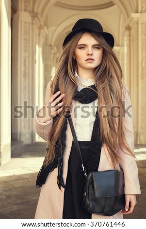 Street portrait of young beautiful lady with long blond hair. Model looking at camera. Female fashion concept. Toned