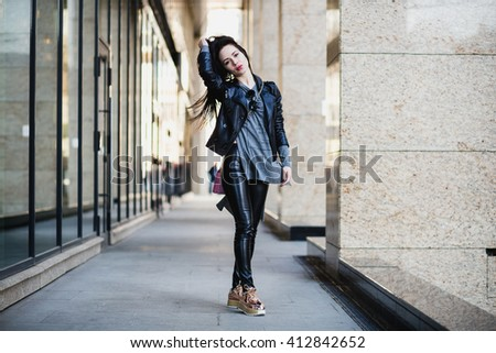 street portrait of young beautiful woman with long black hair, walking though the town