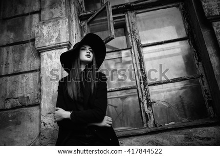 Street portrait of young casual lady in hat, black clothes, red lips