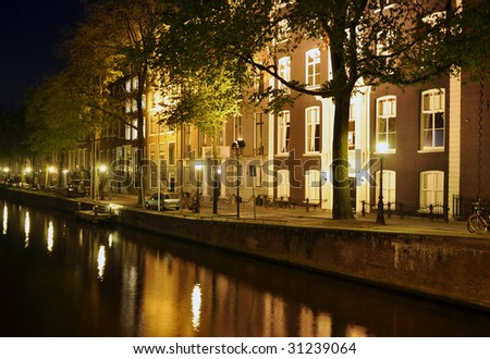 Street scene along a canal in Amsterdam at night