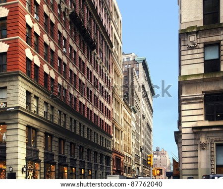 street scenery with house facades in New York (USA) in front of blue sky - stock photo
