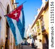 Street  sidelined by decaying buildings in Old Havana with a big cuban flag (square format) - stock photo