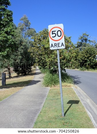 Street sign 50 Area indicating speed limit of 50 kph in Australia. Sign post is slanted or leaning.