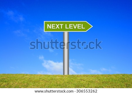 Street Sign showing Next Level in front of blue sky on green grass - stock photo