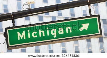 Street sign showing the direction to Michigan.  There is a generic office building in the background of the image. - stock photo