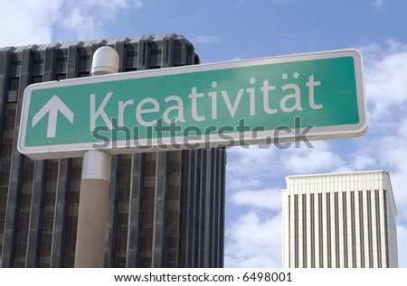 "Street sign with an arrow and the German word ""kreativitaet"" located in a business district - stock photo"