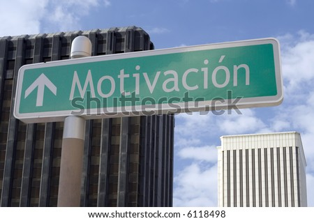 "Street sign with an arrow and the Spanish word ""motivacion"" located in a business district - stock photo"