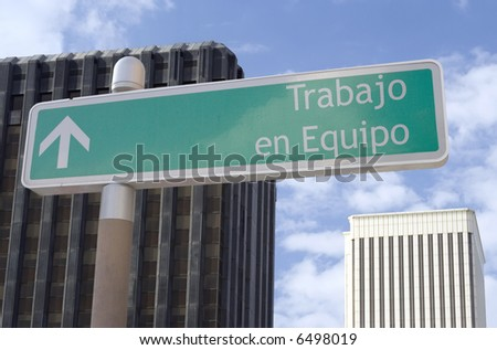 "Street sign with an arrow and the Spanish words ""trabajo en equipo"" located in a business district - stock photo"