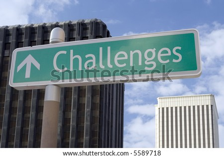 "Street sign with an arrow and the word ""challenges"" located in a business district. - stock photo"