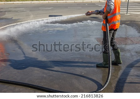 Street sprayed clean with pressurized water, wet cleaning of street. Selective focus. - stock photo