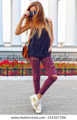 Street style fashion portrait of young sexy woman in crazy jeans heeled sneakers, have trendy blonde ombre hairs. - stock photo