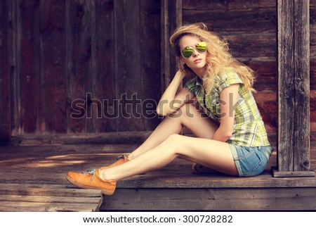 Street Style Fashion Woman Outdoors. Toned Photo with Copy Space. Wooden Background.