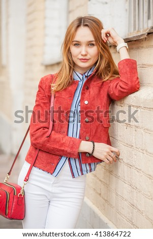 street style of fashionable young woman in red jacket and handbag, white pants, blue shirt - stock photo
