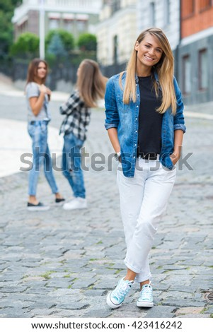 Street style stylish girl. Portrait of young and beautiful girl standing on the street. Her friends are behind her, having fun and good cheerful time - stock photo