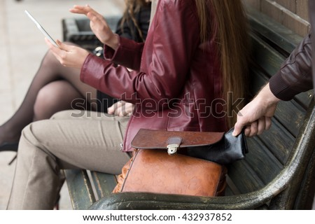 Street thief stealing a wallet from woman bag. Focus on theft hand. Close-up - stock photo